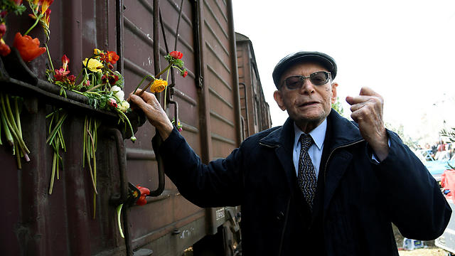 Heinz Kunio, a Jewish survivor of the Holocaust, places a flower on a train wagon during a memorial marking the 74th anniversary of the first deportation of Jews from Thessaloniki to Auschwitz, in Thessaloniki, Greece (Photo: Reuters)