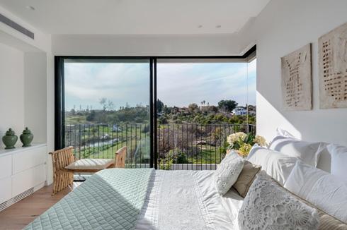 בחדר השינה של ההורים מקיפים החלונות הגדולים את פינת החדר ומרחיבים את תמונת הנוף הנשקף מהם (צילום: עודד סמדר)