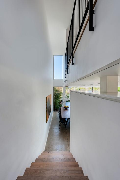 גרם המדרגות אל הקומה השנייה מוסתר מאחורי קיר המטבח. המדרכים מחופים בפרקט אלון, המכסה גם את כל הקומה השנייה (צילום: עודד סמדר)