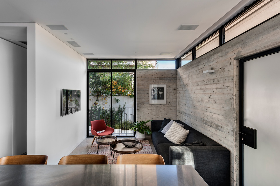 הטלוויזיה נמצאת בפינת המשפחה, מול המטבח. אם המשפחה היססה ביחס לבטון החשוף, והאדריכלים חששו שיצטרכו לטייח את הקירות האלה (צילום: עודד סמדר)