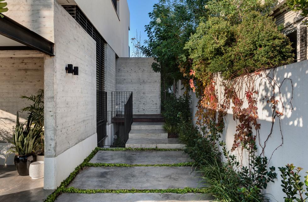 שביל הכניסה לדלת הראשית נמצא בצד הבית. הבית השכן נבנה בסגנון כפרי, וצמד האדריכלים התבקשו לייצר הפרדה ויזואלית ממנו (צילום: עודד סמדר)