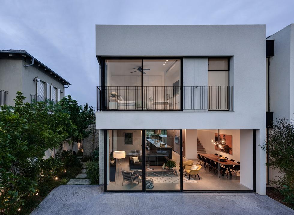 מבט אל הבית מהגינה האחורית. הקומה העליונה בולטת יותר מהתחתונה. מימין נראה החלל הצר שבו ממוקם גרם המדרגות, המשמש גם כהפרדה מהבית הצמוד (צילום: עודד סמדר)