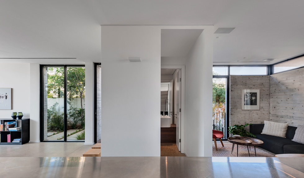 קובייה סגורה ולבנה, שבה מוקמו שירותי האורחים, מפרידה בין הסלון לפינת המשפחה (צילום: עודד סמדר)