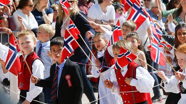 חמקה מהמשבר הכלכלי העולמי. ילדים עם דגל הלאום בנורבגיה (צילום: EPA)
