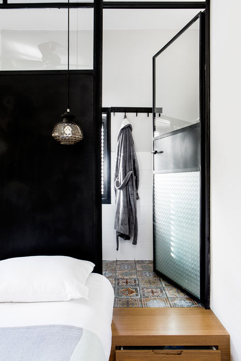 המדרגות המובילות לחדר הרחצה משמשות גם כשידות אחסון, ובמקום קיר נבנתה מחיצת זכוכית כדי לאפשר מעבר אור. כך התאפשר לתכנן חדר רחצה פרטי להורים במרחב המוגבל  (צילום: איתי בנית)