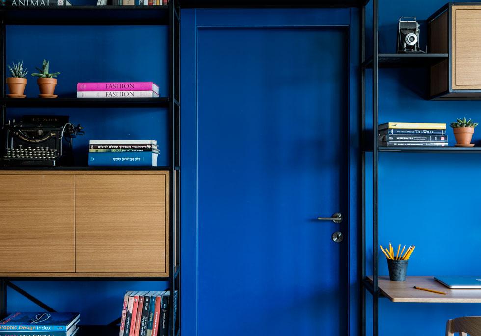 הדלת לחדר ההורים נצבעה בגוון כחול עז זהה לזה של הקיר, כך שכל הקיר הזה דומיננטי ודרמטי  (צילום: איתי בנית)