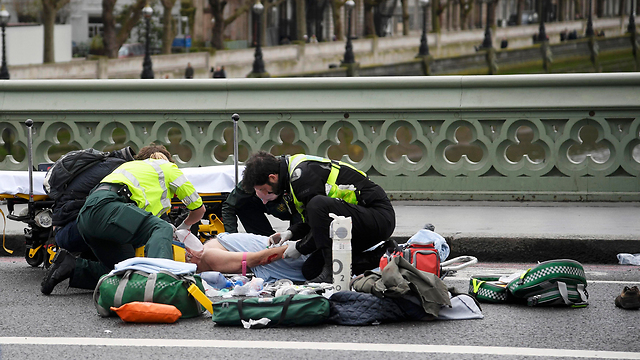 Tending to one of the attack's victims (Photo: Reuters)