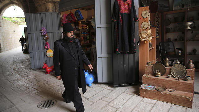 A Palestinian actor dressed as ultra Orthodox Jew walks during a shoot. (Photo: AP)