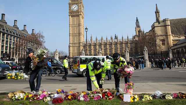 Police arrange flowers in memory of attack (Photos: Getty Images and AFP)