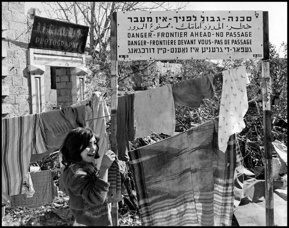 A little girl hangs up laundry below a sign marking the border between east and west Jerusalem, 1954 (Photo: David Seymour)