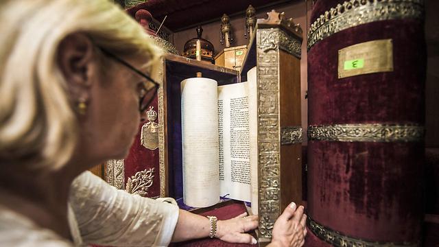 The president of the Egyptian Jewish Community, Magda Shehata Haroun, before Torah scrolls (Photo: AFP)