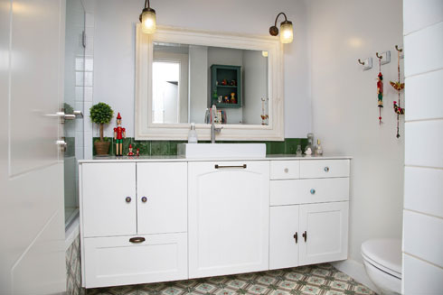 מקלחת הילדים, כמו מקלחת ההורים, מרוצפת במרצפות מצוירות. הקיר צבוע בצבע שמן ודמויות פינוקיו מוסיפות מגע אישי (צילום: שרית גופן)