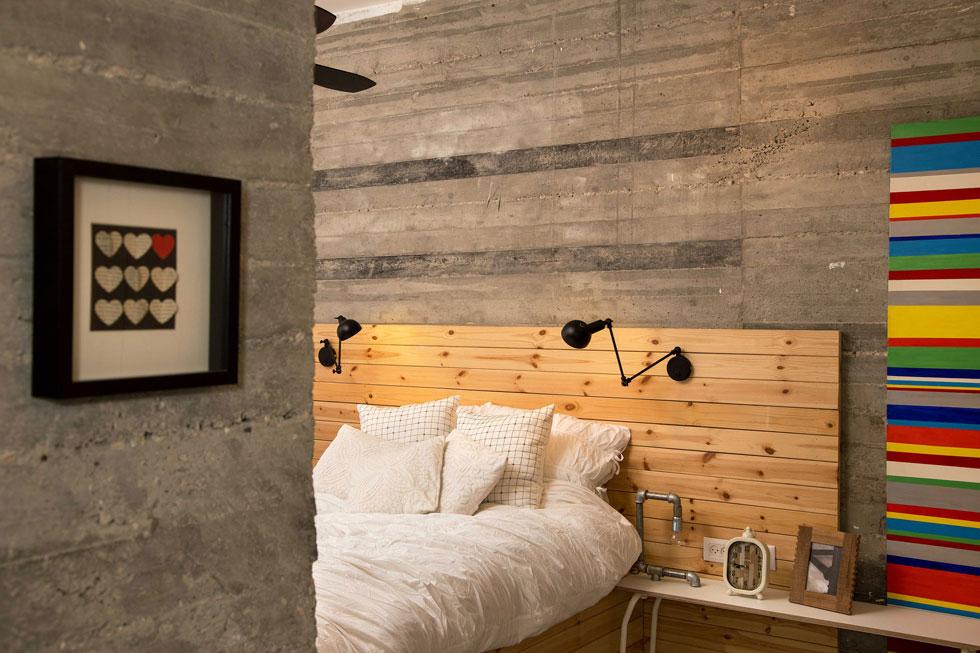 בחדר ההורים קירות בטון חשוף. לוחות העץ של המיטה מטפסים על הקיר, ולצדם ציור מפוספס צבעוני, שבעלת הבית ציירה לפני שנים (צילום: שרית גופן)