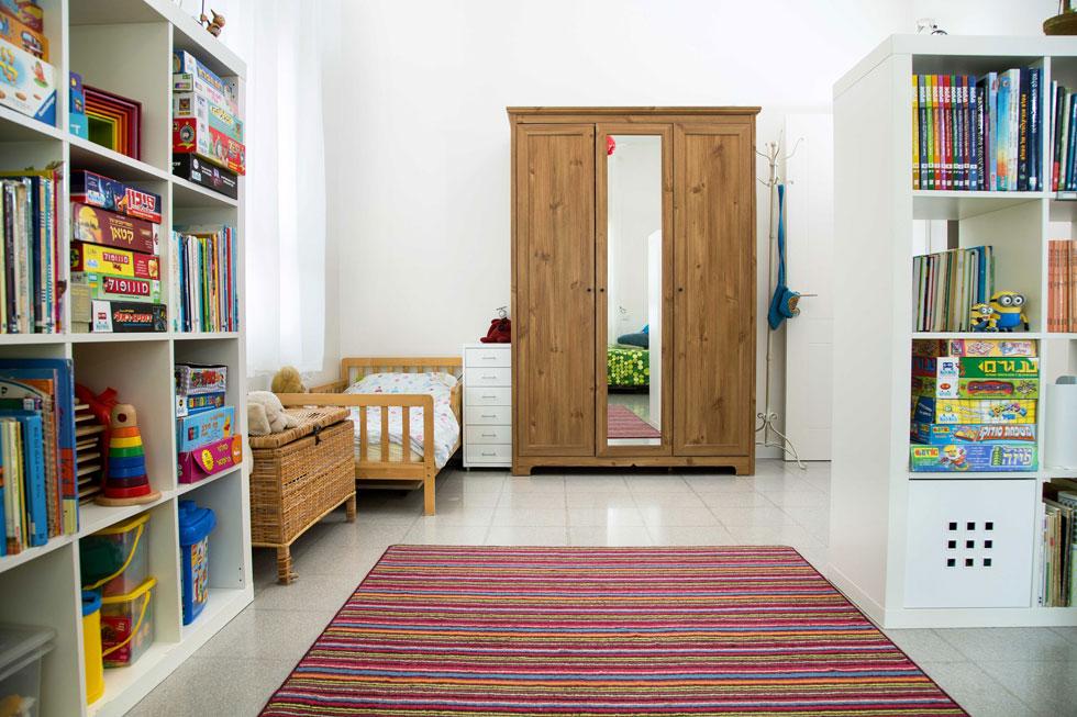 שלושת הבנים ישנים בחדר אחד, שתוכנן כך שבעתיד ניתן יהיה לחלקו לשניים. לכל ילד פינה משלו, עם ספרייה ושידת מגירות צרה ליד המיטה (צילום: שרית גופן)