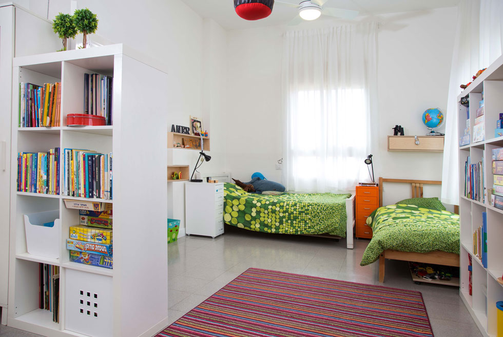 לבלגן הרגיל נמצא פתרון מקורי: לכל ילד פלטת עץ על גלגלים שעליה הוא יכול לבנות בלגו או לשחק. בתום המשחק נכנסת הפלטה מתחת למיטה, וכך נשמר המשחק וגם הסדר בחדר (צילום: שרית גופן)