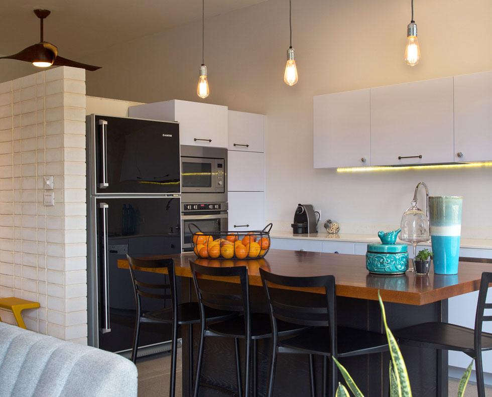 ארונות המטבח עשויים מפולימר שנראה כעץ צבוע בתנור, והידיות משתנות. נישה מיוחדת תוכננה לקופסאות הדגנים (צילום: שרית גופן)