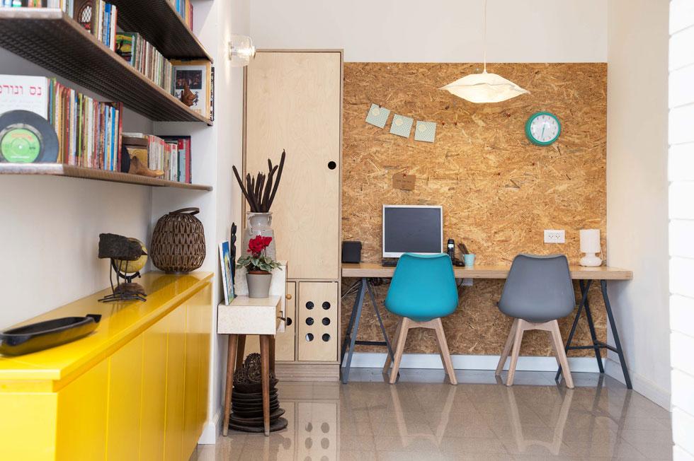 """בפינת המחשב שני כיסאות אימס צבעוניים, ולוח עץ גדול משמש לתליית פתקים, ציורים ועוד. """"רציתי פינה גלויה"""", אומרת פרידמן, """"כך שלא יווצר מצב שהילדים יגלשו באתרים אסורים"""". משמאל לשולחן יש ארון למעילים ותיקים, עם תא מיוחד, מחורר, לכונן המחשב  (צילום: שרית גופן)"""