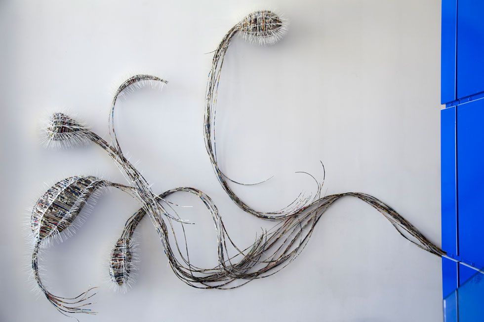 התערוכה מתחילה כבר בכניסה לבניין, עם צמח הנייר של אבי סיביליה, שמטפס על הקיר ומלווה את גרם המדרגות (צילום: הדר סייפן)