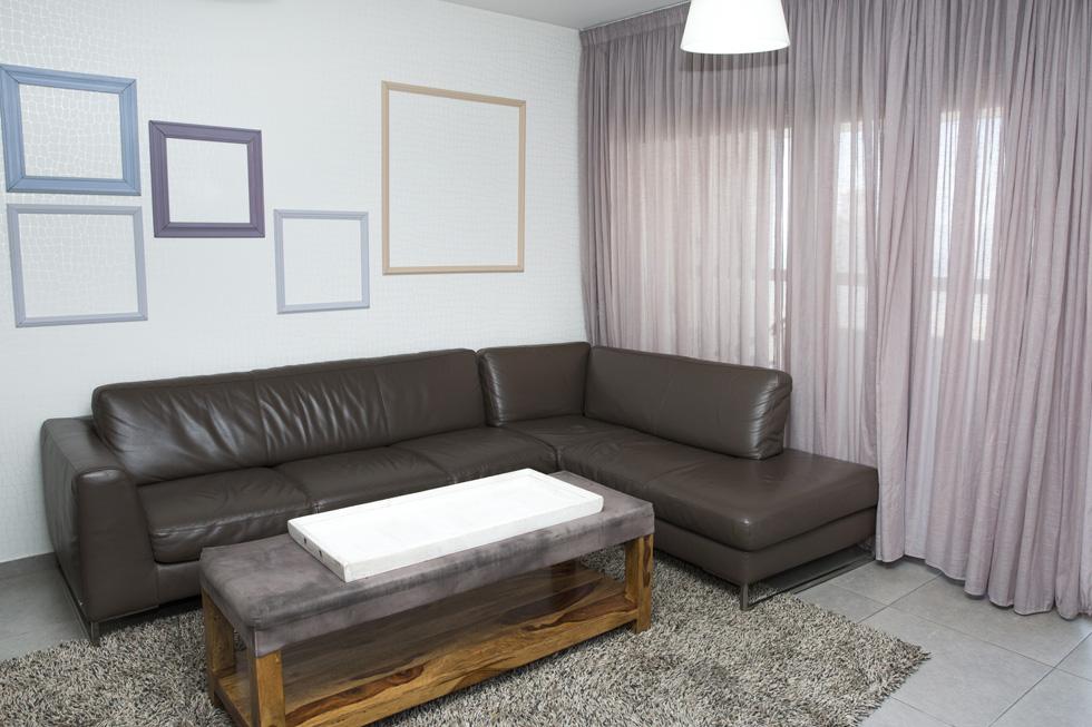 את קירות הסלון מקשטות מסגרות ריקות (צילום: ענבל מרמרי)