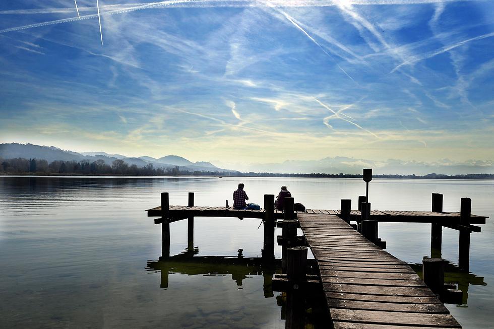 שתי נשים יושבות במזח על גדות נהר פאפיקון בשווייץ (צילום: EPA)