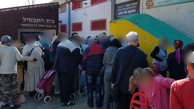 קשישים ועולים חדשים ממתינים בתור לקבלת מצרכים לפסח בלוד (צילום: עומרי אפרים)