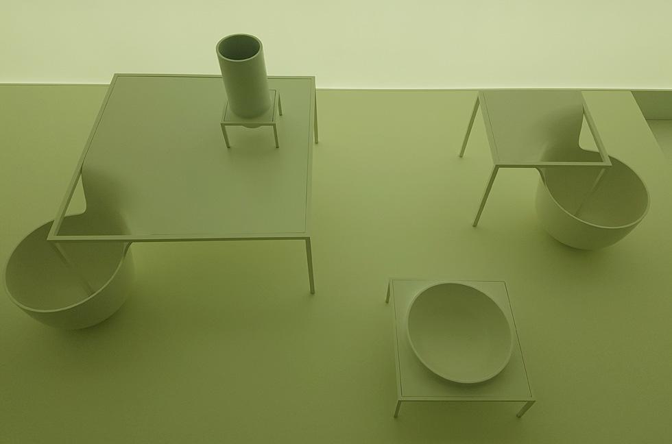 """על רקע קיר אור לבן-חלבי, מוצגים בין היתר רהיטים שקווי המתאר שלהם אינם שגרתיים, לכאורה שגויים ועדיין מושלמים. הצופים מוזמנים להשלים את החסר בדמיון, כמו במלים מחוסרות-אותיות (צילום: איתי כ""""ץ)"""