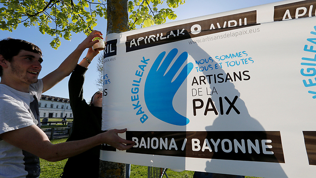 A young protestor puts up a sign against the ETA after it announces it is handing over its weapons (Photo: Reuters)