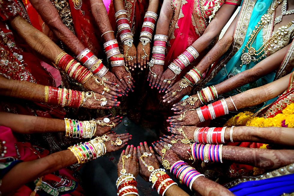 יותר מ-15 זוגות צעירים נטלו חלק בחתונה המונית שנערכה בעיר בופאל שבהודו (צילום: EPA)