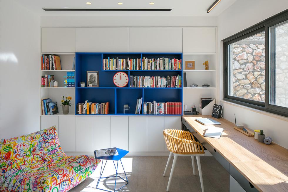 שולחן ארוך נבנה מתחת לחלון הפונה למסלעה ולעצי זית ותיקים. על קיר שלם ספרייה בלבן וכחול. פוף צבעוני נבחר בינתיים, עד שייתלה מסך טלוויזיה ומולו ספה (צילום: עוזי פורת)