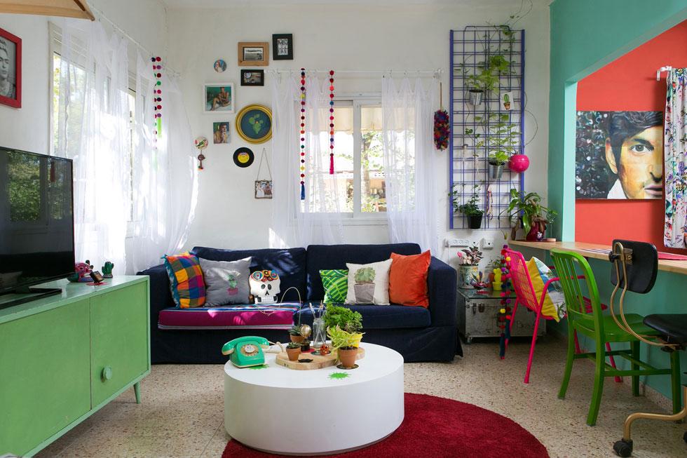 הבית מורכב משני חדרים ששימשו רווקים צעירים בקיבוץ. עיקר ההוצאה הייתה על הריסה חלקית של הקיר בין החדרים. במקומו בנה גלימידי שולחן אוכל. הספה הישנה מרופדת בקורדרוי כחול, אך הכריות והכיסאות הצבעוניים שוברים את הסולידיות שלה (צילום: שירן כרמל)
