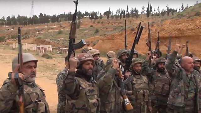 Raising their guns in salute to Assad