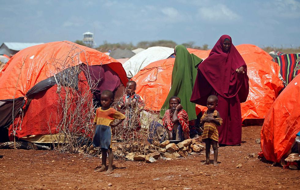 משפחה סומלית שנעקרה מביתה בעקבות הבצורת באזור מגוריה מערבית לבירה מוגדישו (צילום: רויטרס)