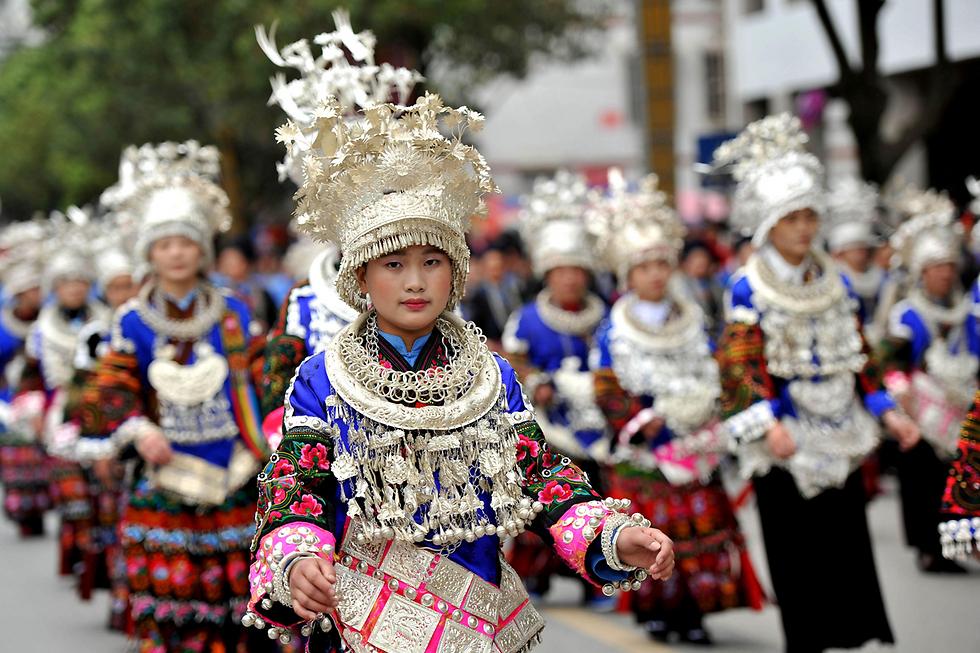 נשים מהמיעוט האתני מיאו משתתפות במצעד תחפושות מסורתי במחוז גוויג'ואו שבסין (צילום: AFP)