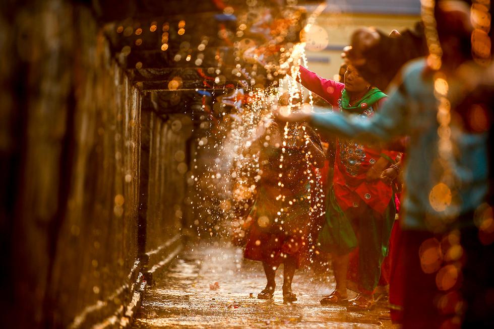 מאמינים הינדים מתקלחים במהלך חגיגות פסטיבל ירח מלא בקטמנדו, נפאל (צילום: EPA)