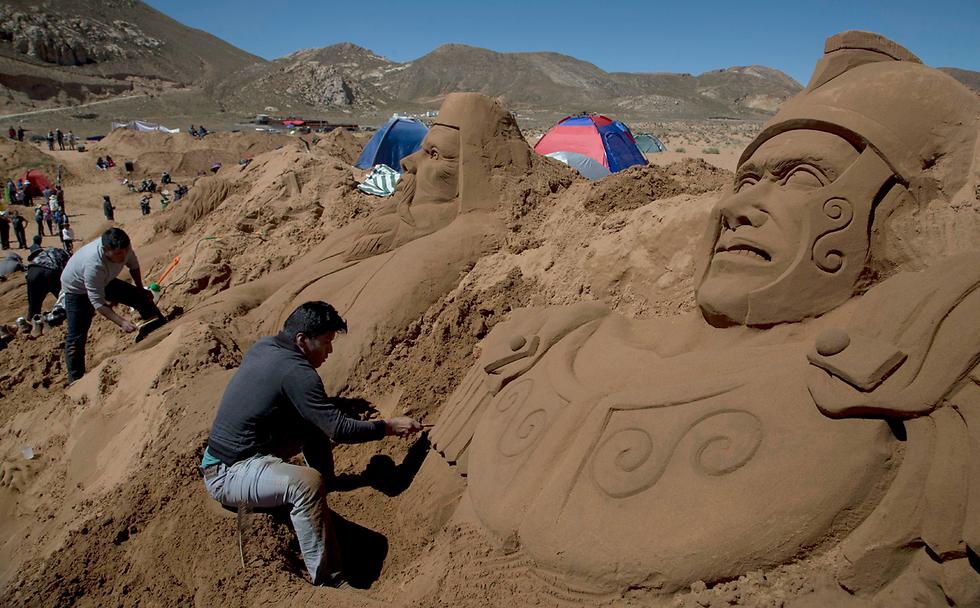 """אמנים מפסלים בחול במהלך חגיגות """"השבוע הקדוש"""" בפאתי אורורו, בוליביה (צילום: AP)"""
