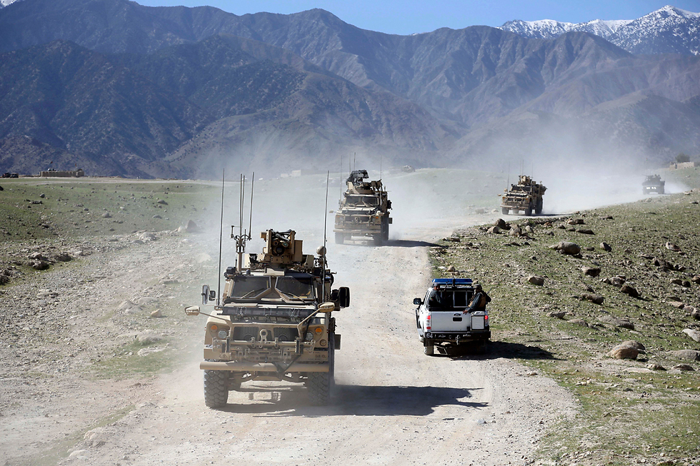 """כוח סיור אמריקני ואפגני בכפר פנדולה, הסמוך למקום שאותו הפציצה ארה""""ב מעוז של דאעש במחוז אצ'ין עם """"אם כל הפצצות"""" (צילום: AP)"""