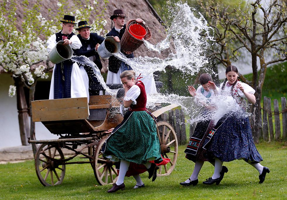 גברים מתיזים מים על נשים כחלק מחגיגות חג הפסחא המסורתיות בכפר בהונגריה (צילום: רויטרס)