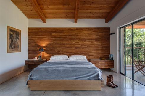 רצפת בטון, קיר ותקרת עץ בחדר ההורים (צילום: עודד סמדר)