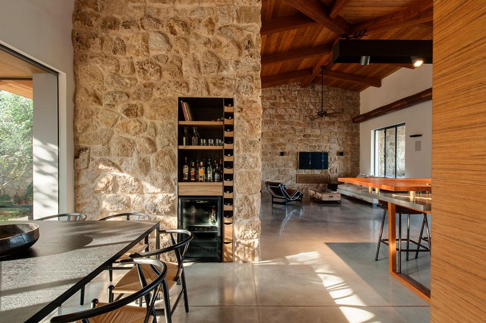 בקיר האבן שמפריד בין פינת האוכל לבין המבואה הוטמעו ארון (מצד הדלת) ומקרר יין (צילום: עודד סמדר)