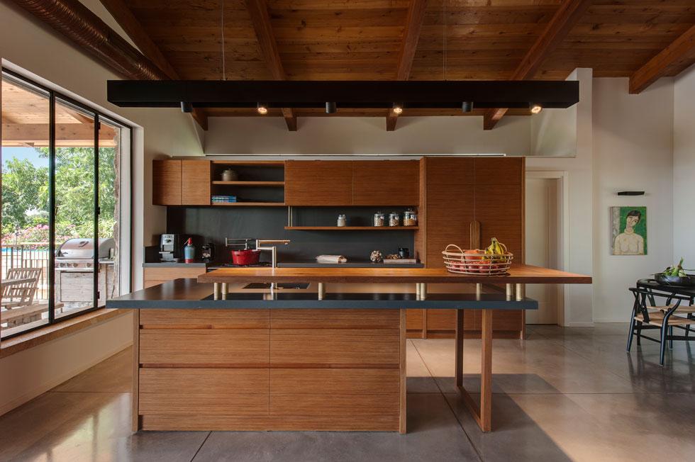 יחסית לשטח הבית, המטבח אינו גדול, אך רואים ממנו הכל - משער הכניסה, דרך הסלון ובריכת השחייה, ועד קצה הנחלה (צילום: עודד סמדר)