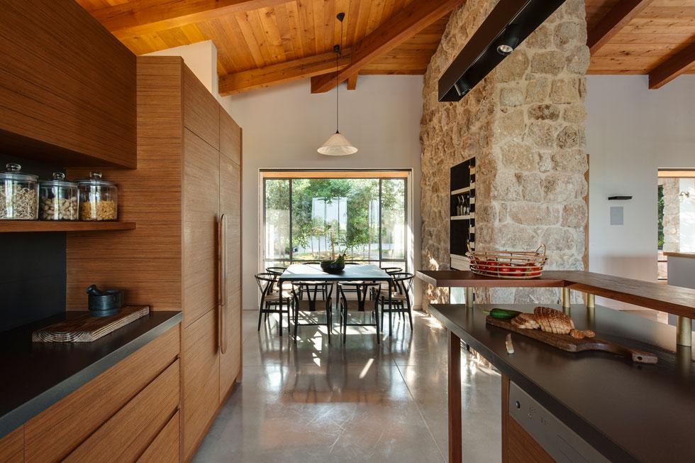המטבח משלב עץ טיק ומשטחי נירוסטה. פינת האוכל ממוסגרת בחלון שבולט החוצה ובקיר אבן, ומופרדת מעט מהסלון (צילום: עודד סמדר)