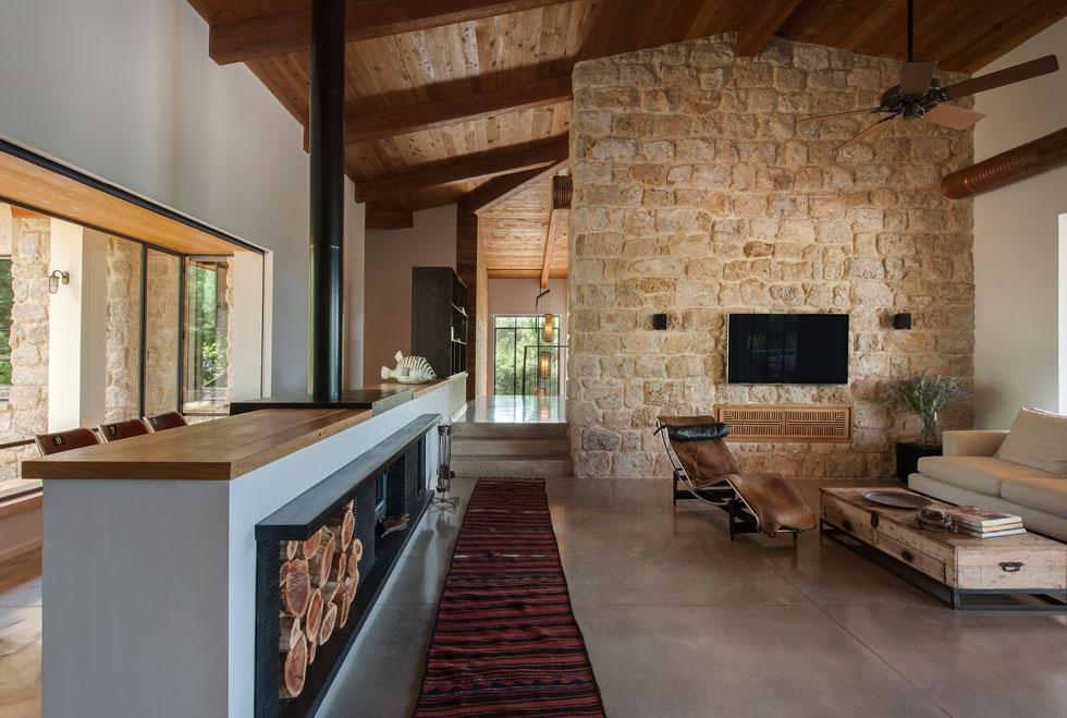 הסלון מוגדר בקיר אבן מאסיבי, שיחד עם שלוש המדרגות מפריד בין האגף הציבורי של הבית לאגף הפרטי (צילום: עודד סמדר)