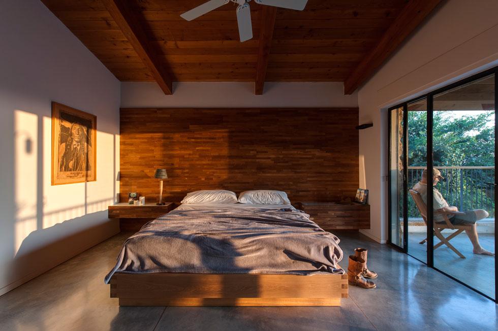 באגף ההורים קיר זכוכית משקיף אל הגן האחורי, ומרפסת פרטית שבה הוצבה אמבטיית עץ. המיטה נשענת על קיר מצופה עץ טיק (צילום: עודד סמדר)
