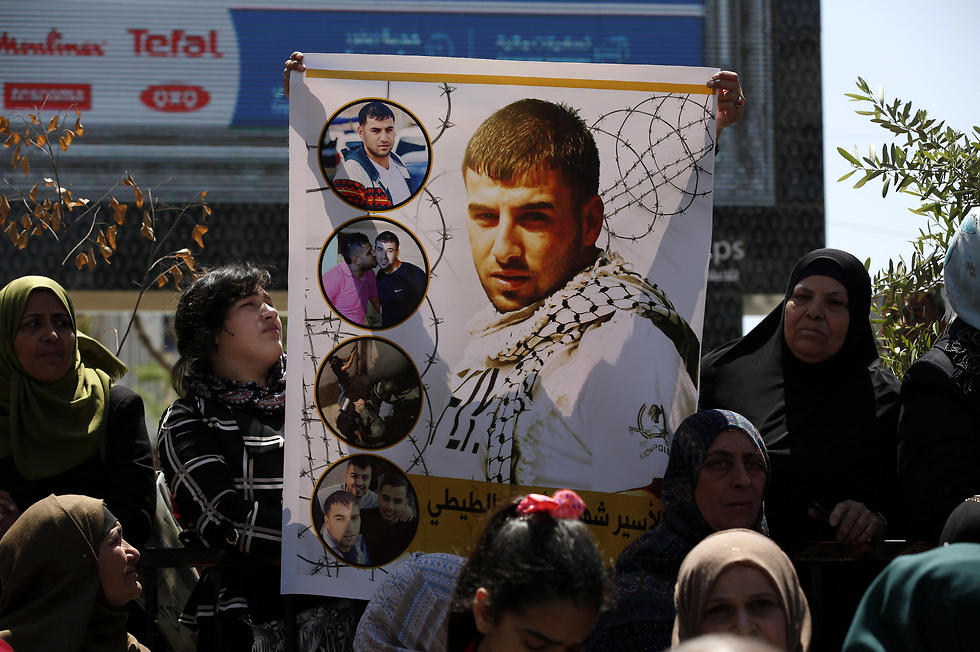 Palestinians hold pictures of their relatives held in Israeli jails during a supportive rally calling for the release of Palestinian prisoners in Israel, in the West Bank city of Hebron on Monday (Photo: EPA)