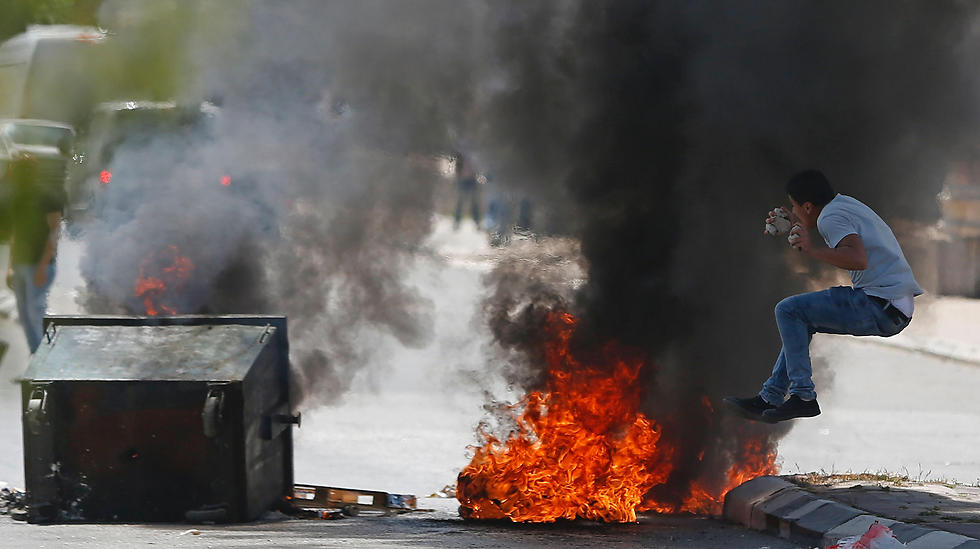 A Palestinian protester jumps near burning tires during clashes with Israeli security forces following a demonstration in the West Bank town of Bethlehem to show their support for Palestinians imprisoned in Israeli jails. (Photo: AFP)