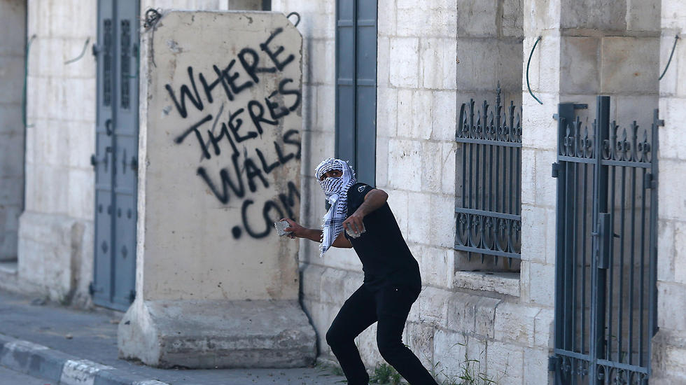 A Palestinian protester hurls stones towards Israeli security forces during clashes following a demonstration in the West Bank town of Bethlehem (Photo: AFP)