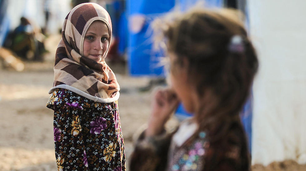 Displaced Iraqi girls who fled Mosul look at each other while standing outside at the Hammam al-Alil camp, south of Mosul, on April 6. (Photo: AFP)