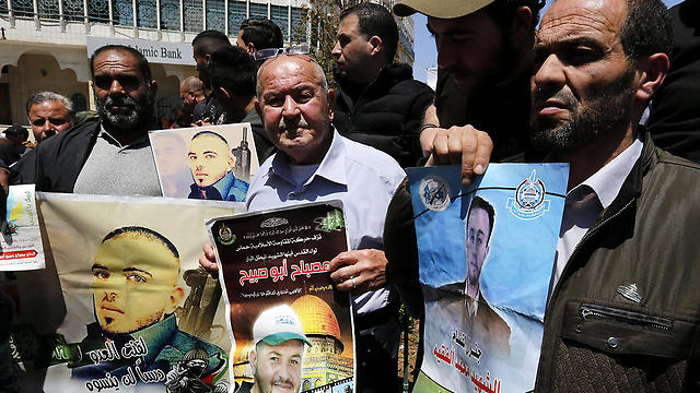 Palestinians hold pictures of their relatives held in Israeli jails during a supportive rally calling for the release of Palestinian prisoners in Israel, in the West Bank city of Hebron last week (Photo: EPA)