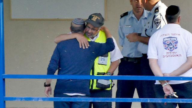 אביו של איתמר, שמעון אוחנה, מחבק את כוחות ההצלה (צילום: אפי שריר) (צילום: אפי שריר)