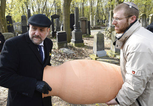 Rabbi Michael Schudrich, left, and Rabbi Moshe Bloom carry a clay jar containing fragments of old Torah scrolls (Photo: AP) (Photo: AP)